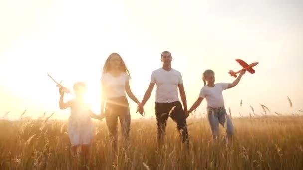 Menschen im Park. glückliche Familiensilhouette Spaziergang mit einem Spielzeugflugzeug. Mama, Papa und Töchter gehen Händchen haltend durch den Park. glückliches Familienkinderkonzept. Eltern und Kind zu Fuß zurück Silhouette Traumflugzeug