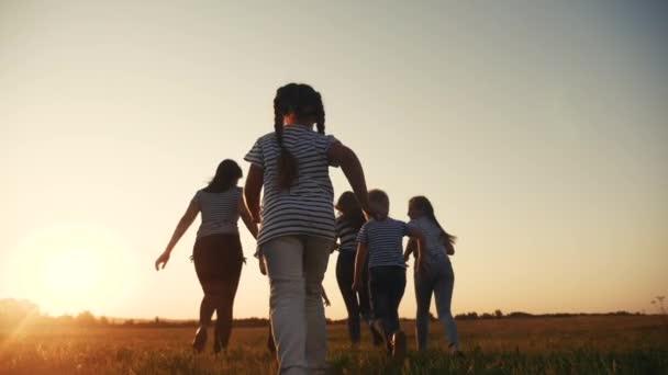 šťastné rodinné děti spolu běhají v parku při západu slunce silueta. lidé v konceptu parku. šťastný rodinný radostný běh. zábava šťastná rodina a malé dítě léto dítě sen koncept