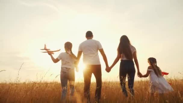 lidi v parku. šťastná rodinná silueta procházka s letadýlkem. Máma táta a dcery chodí v parku a drží se za ruce. koncepce snů šťastných rodinných dětí. rodiče a dítě letadlo chůze zpět silueta