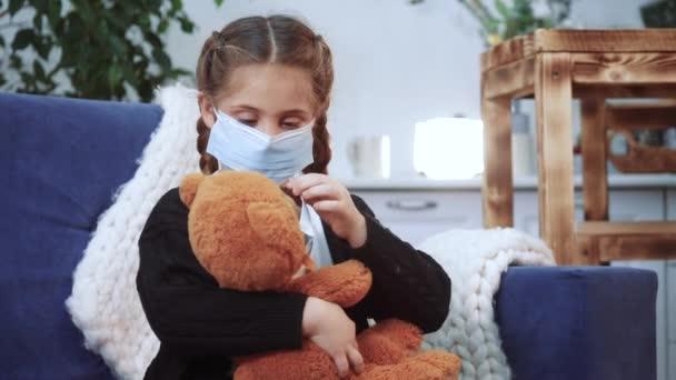 gyermek lány orvosi védő maszk játszani plüssmackó maradjon otthon. pandémiás koronavírus koncepció. Lány gyerek arc orvosi maszkban egy plüssmacival. lány a coronavirus karantén ideje alatt covid -19
