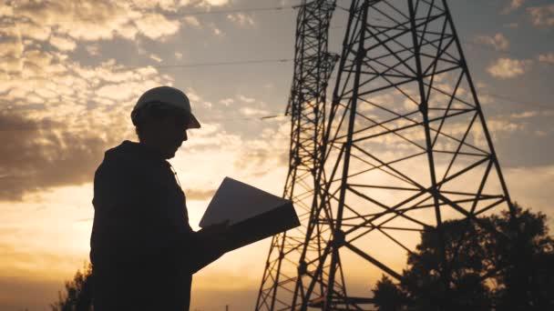 silueta elektrikáře, který pracuje vedle energetického západu slunce na elektrické nosné věži. elektrická vysokonapěťová věž. elektrotechnik zkontroluje napětí elektrického pylonu