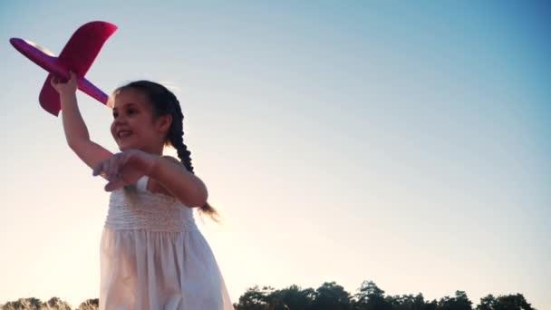 boldog vidám lány gyermek fut egy repülővel. Kölyök sziluett játszani sík. boldog családi álom szabadság repülőgép koncepció. lánya gyerek fut a búzamezőn naplementekor tartja a kezében álom játék repülőgép