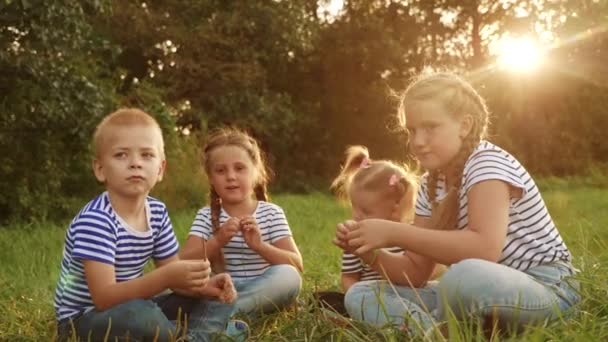 group of children are sitting in the park on the grass talking. kid dream happy family concept. a group of kid relaxing in the park talking to each fun other happy family. people in the park