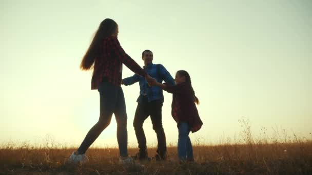 glückliche Familie Mama Papa und Tochter spielen Runde Kreis Silhouette bei Sonnenuntergang. Menschen im Park-Kind-Traum-Konzept. glücklich Familie Eltern mit kleinem Kind Kind Tochter spielen im Park auf Gras Händchen halten Spaß