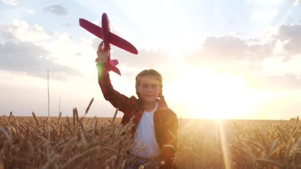 Lány gyerek fut egy játék repülőgép naplementekor. gyerek álom gyermekkori koncepció. A lány gyerek egy repülő játék sziluettel rohangál a parkban. gondtalan gyermek szórakoztató álom szabadban sziluett. emberek a parkban