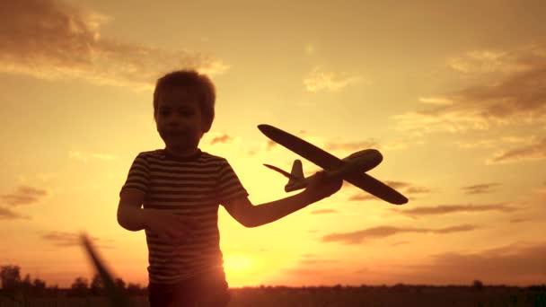 šťastný chlapec dítě jít běží s letadlem hrát pilot chce létat. dětská silueta hrát letadla. životní styl šťastný rodinný sen svobody koncept. syn běží na pšeničném poli při západu slunce drží v rukou