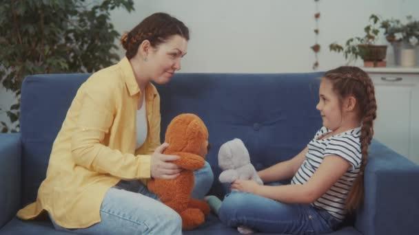 Máma si hraje s dcerou doma v plyšovém medvídkovi. Happy rodina zábava dítě sen zůstat doma koncept. Máma si hraje s dcerou na gauči sedící s plyšovým medvídkem