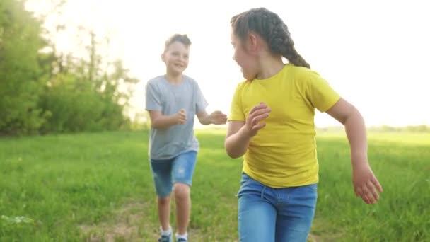 Dohonit. Děti spolu sní při západu slunce v parku. šťastní rodinní lidé v parku konceptu. chlapec a dívka si hrají na útěk. malé dítě pobíhající na zelené louce. happy rodina zábava dítě sen koncept