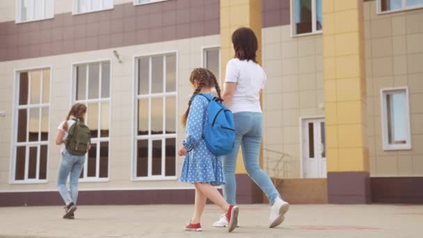 Vissza az iskolába. Anya és lánya kéz a kézben járnak az iskolába, hogy tanuljanak. oktatási képzési támogatás koncepciója. gyerek séta az életmód iskolába egy hátizsák. Anya lánya siet az iskolába. családi nap