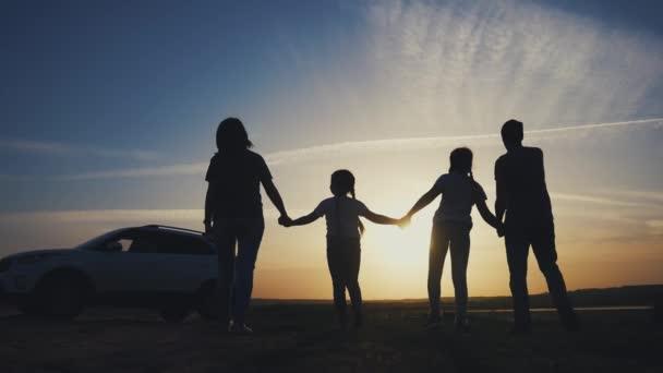 Menschen im Park. glückliche Familie eine Silhouette Spaziergang bei Sonnenuntergang. Auto reisen Kindertraum Konzept. Glückliche Familieneltern und lustige Kinder gehen neben dem Auto spazieren. Familienspaziergang bei Sonnenuntergang neben Auto