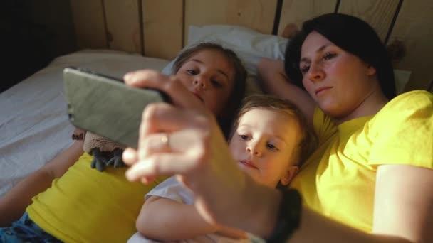 šťastná rodina doma. Máma dítě syn a dcera sledování online video zábava na smartphone gadget ležící v posteli doma. sluneční svit z ranního rozhovoru. šťastný rodina video on-line maminka a dítě děti