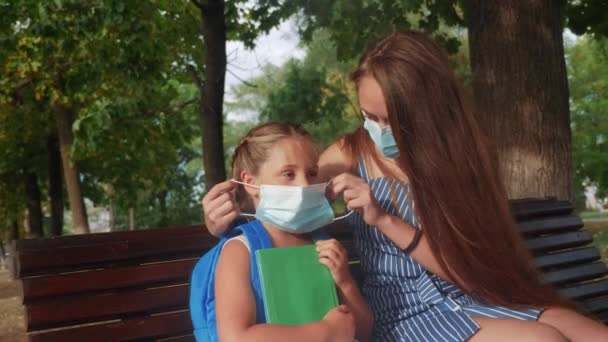 mom puts on a protective mask for her daughter in the park on a bench. coronavirus social distance concept. mom puts on a protective mask for schoolgirl daughter. kid dream covid 19 park concept