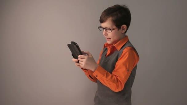 chlapec teenager hrál tabletu keen překvapen brýle šedé pozadí