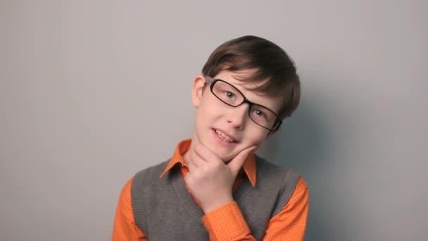 dospívající chlapec úsměvem zkušenosti štěstí drží ruku na bradě v brýlích na šedém pozadí desetiletí