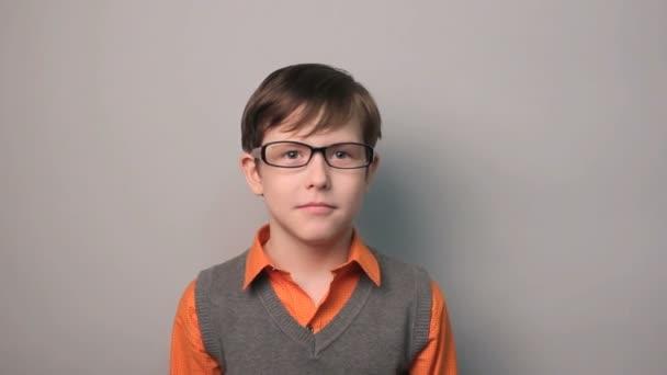 chlapec pubertě překvapení štěstí radosti vlny ruce deset let v brýlích na šedém pozadí