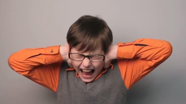 tinédzser fiú zárt a fülét a kezek hangos szemüveg szürke háttér