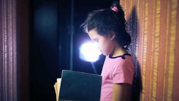 Dospívající dívka dítě čtení knihy stoje proti zdi v bytě obracející stránky