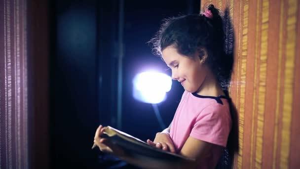 Dospívající dívka dítě čtení kniha přitom stát proti zdi v bytě obracející stránky