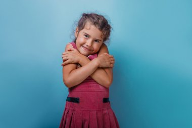 Girl European appearance decade hugging herself on a blue  backg