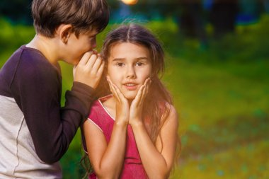 boy girl whispers in the ear secret rumors says in nature photos