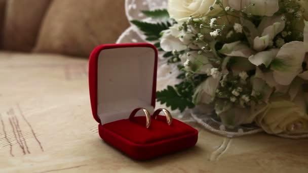 Fedi nuziali in rosso scatola nel video di bouquet da sposa di sfondo