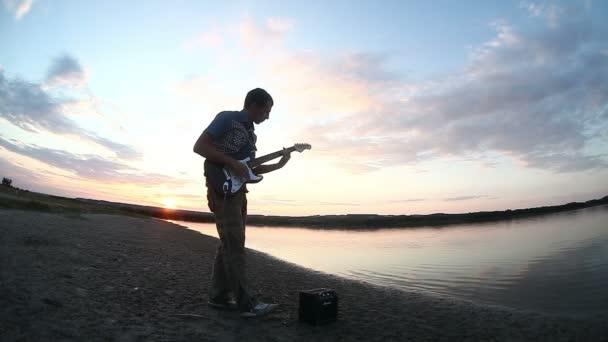 muž muž kytarista pouliční hudebník hraje na elektrickou kytaru při západu slunce vodou slunce zapadá