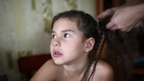 mother makes daughter female girl hair braid  sitting in the morning,