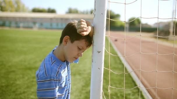 Teenager-Junge ärgert Niederlage, indem er Torpfostennetz Stadionrasen klopft