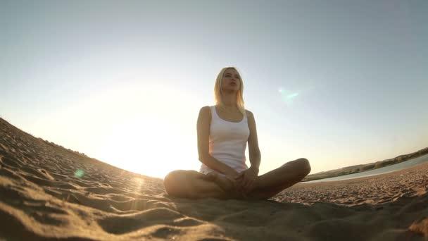 Frau in Weiß sitzt auf Sand Meditation gesunder Lebensstil Sonnenuntergang Sonne geht unter, Silhouette gegen den Himmel Yoga