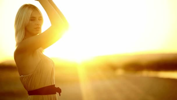 Fiatal csábító lány szőke nő portréja naplemente silhouette szexi lassú sárga sivatagi homok flare sunbeam nap