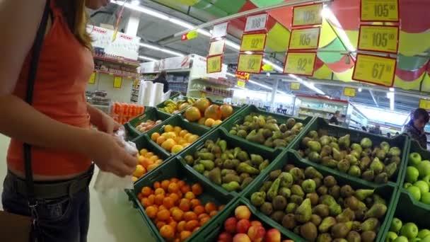 žena zvolí hrušky jablka v obchodě dívka trh