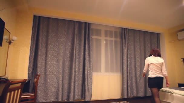 Rückansicht eines Mitarbeiters des Administrators junge Frau öffnet die Vorhänge am Fenster für die Eröffnung eines Hotelzimmers