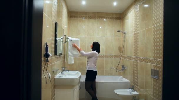 Maid nő teszi tisztítás a fürdőszobában törölköző kiegyenesedik