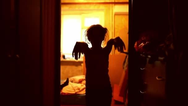 dospívající dívka v zombie je oranžová silueta natažené ruce