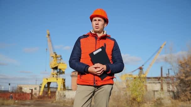 muž stavební dělník v oranžovou helmu drží dokumenty v pozadí modré oblohy a jeřáb