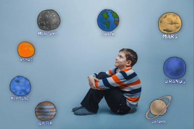 Teen boy sitting hugging her knees and looking at the planets of