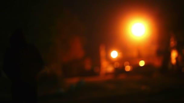 silueta muže v kápi je noční světlo lucerny zloděj pachatele