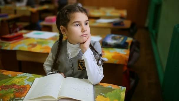 Školačka dívka sedí u stolu u okna a díval myšlení třídy školy