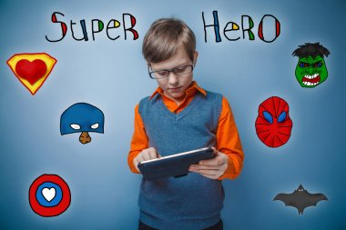 Teen boy retro style works enthusiastically on the tablet superh