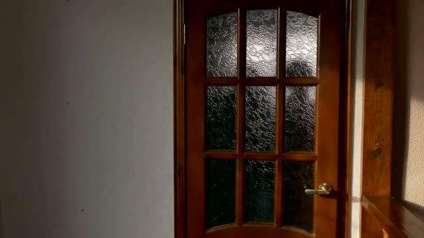 room with wooden door after door silhouettes of people walking