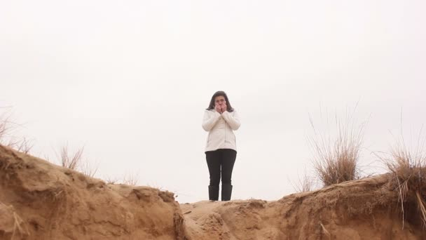 Woman girl stands in the autumn on the nature of the sand cliff cold  freezing