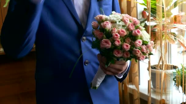 man groom lifts bridal bouquet at wedding table accessories