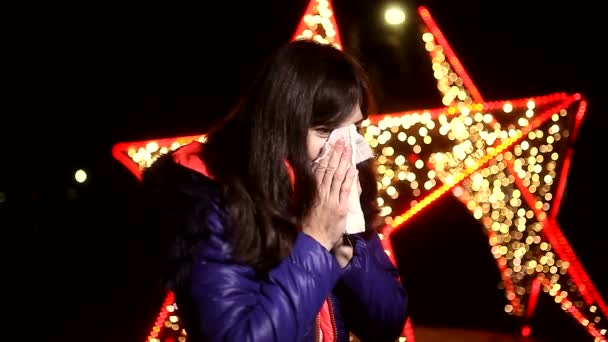 woman sneezing into a handkerchief cold influenza winter night bokeh stars