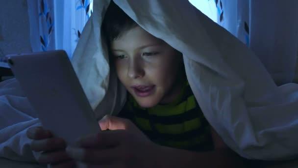 chlapec hrát tabletu večer pod dekou