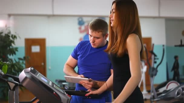woman runs on a treadmill, man with tablet manager, a gym sport a healthy lifestyle