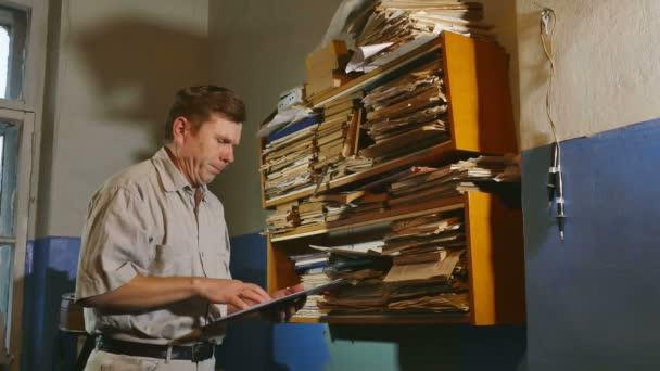 účetní starý muž úředník retro dotkne papíru ve staré kanceláři