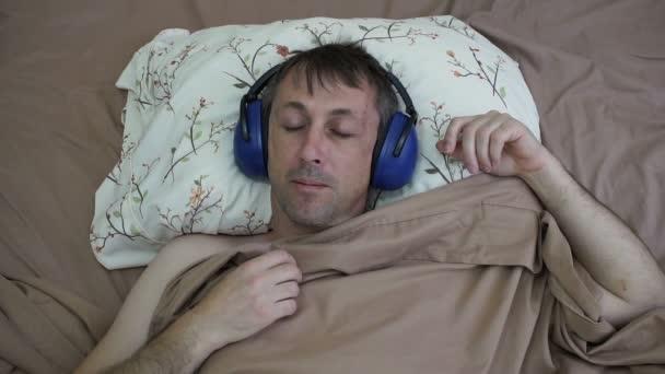 Muž spí ve dne s Chrániče uší