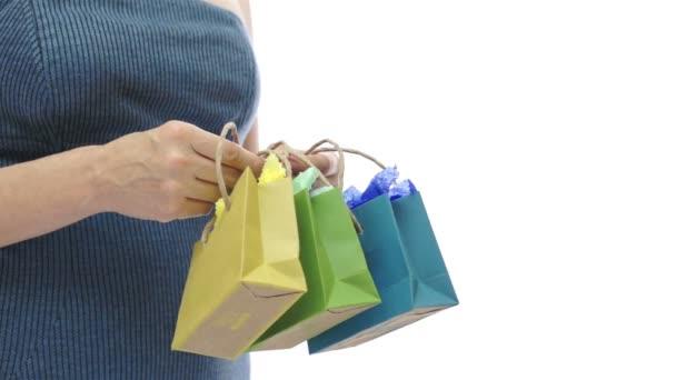 Žena a tři malé barevné dárkové tašky
