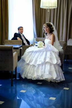 Beautiful bride and the groom sit at a table in the hotel bar