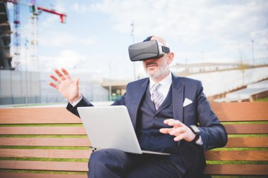 businessman sitting on bench using 3D viewer